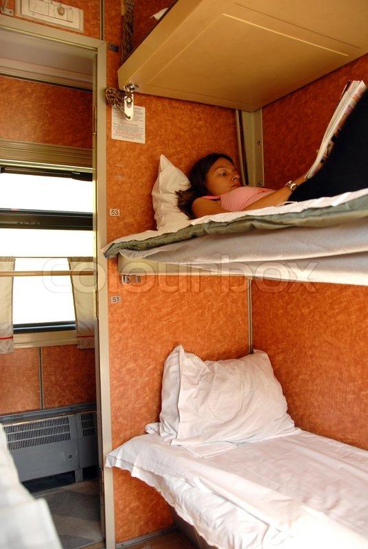 Girl lying and reading a book in sleeping wagon in train ...