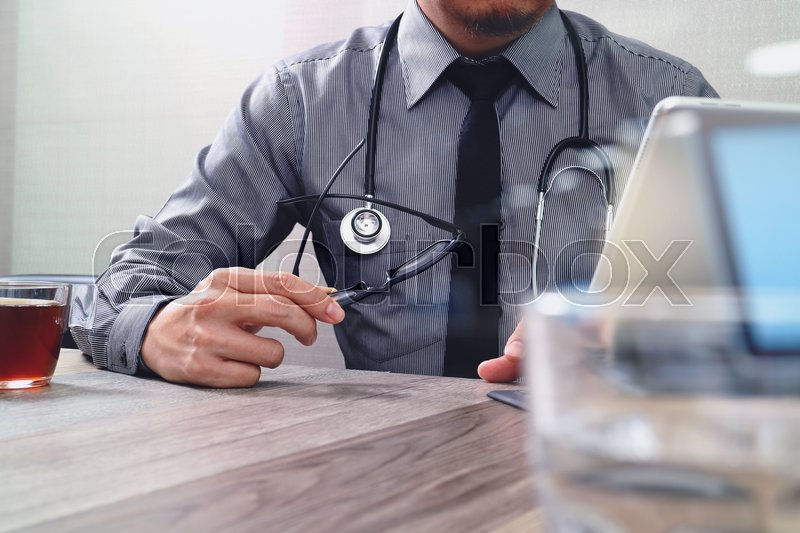 Smart medical doctor hand working with smart phone,digital tablet computer,stethoscope eyeglass,on wood desk,filter effect, stock photo