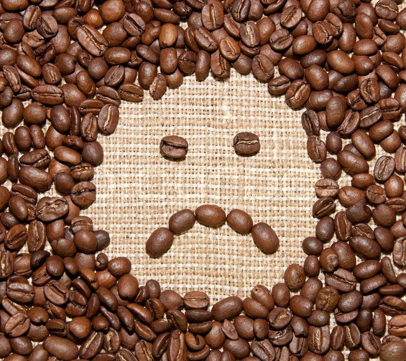Coffee beans sad smile on burlap background, stock photo
