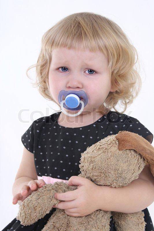 Kleines mädchen mit spielzeug zu weinen über weißem