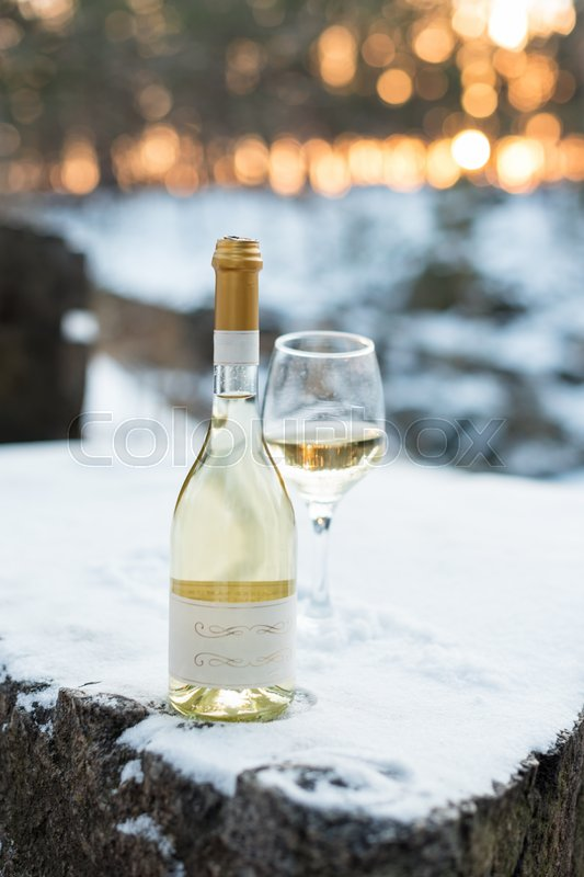 Love, romance, holiday, New Year celebration concept. Bottle and glass of white wine chilled by snow in winter forest on sunset, stock photo