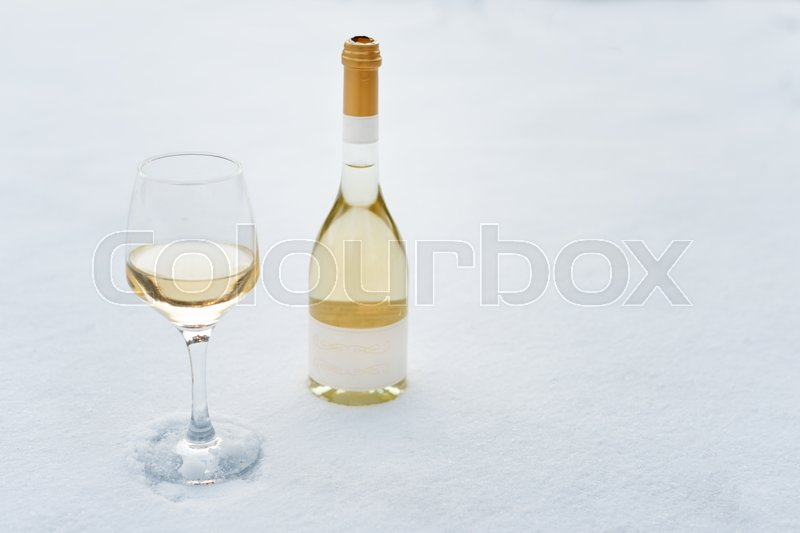Love, romance, winter holidays, New Year celebration concept. Bottle and glass of white wine chilled by snow, stock photo