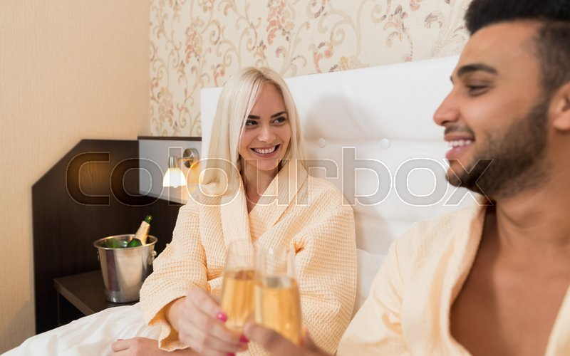 Young Couple Lying In Hotel Bed Drink Champange, Happy Smile Hispanic Man And Woman Lovers In Bedroom, stock photo