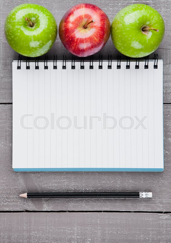 Writing pad with healthy apples as diet plan idea on wooden board, stock photo