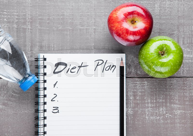 Writing pad with apples and water as diet idea on wooden board, stock photo