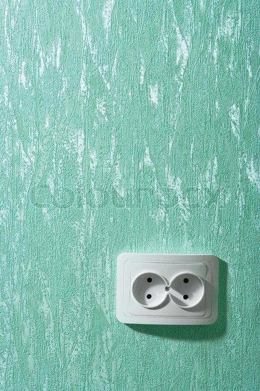 Electric wall plug at a green wall, stock photo