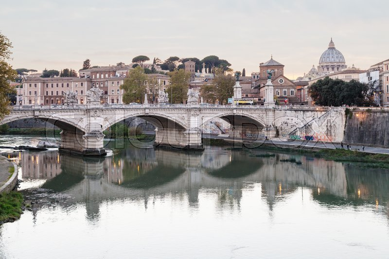 Travel to Italy - Rome city skyline with Tiber River, and bridge Ponte Vittorio Emanuele II, dome of Saint Peter Basilica in Vatican in evening twilight, stock photo