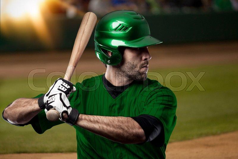 Baseball Player with a green uniform on baseball Stadium, stock photo
