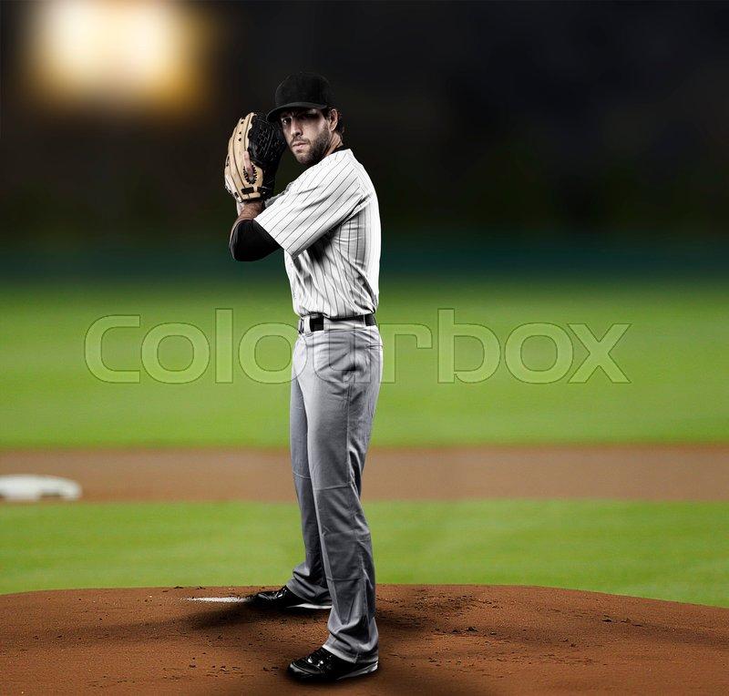 Pitcher Baseball Player with a white uniform on baseball Stadium, stock photo