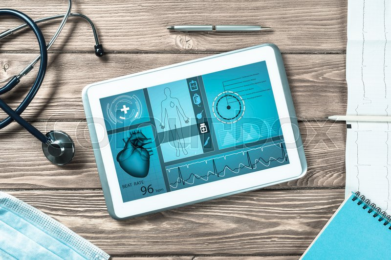 White tablet pc and doctor tools on wooden table, stock photo