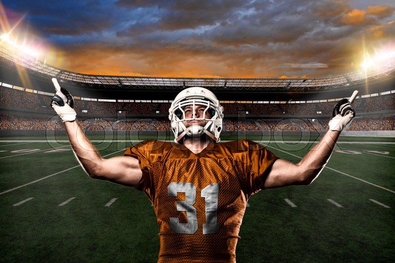 Football Player on a Orange uniform celebrating on a stadium background, stock photo