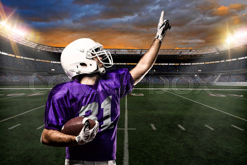 Football Player on a purple uniform celebrating on a stadium background, stock photo