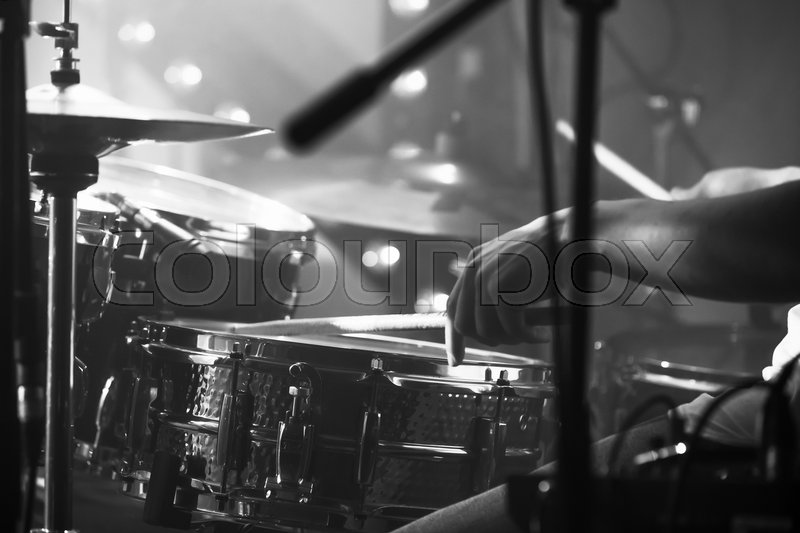 Black and white live music background, drummer plays with drumsticks on rock drum set. Closeup photo with soft selective focus, stock photo