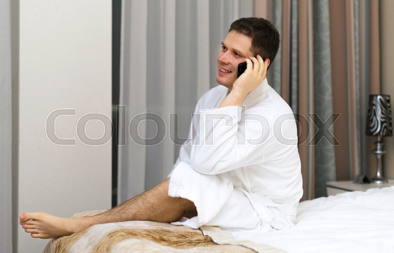 Happy man in bathrobe with mobile phone in hotel room, stock photo