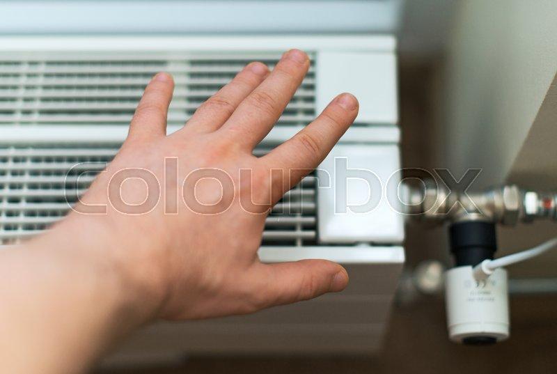 Man\'s hand checking temperature of heating radiator, stock photo