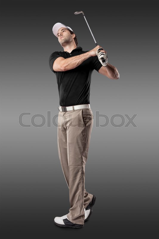 Golf Player in a black shirt taking a swing, on a black Background, stock photo
