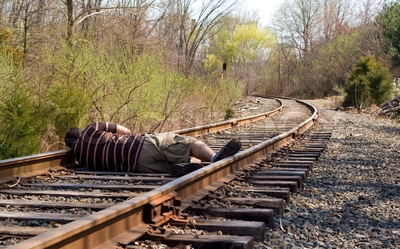 Levers Train Tracks O N : A man laying on the railroad tracks not exactly