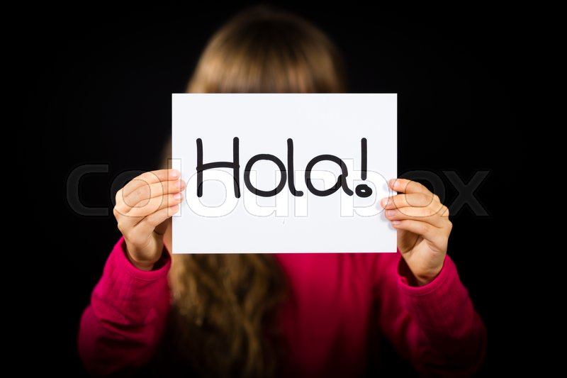 Studio shot of child holding a sign with Spanish word Hola - Hello, stock photo