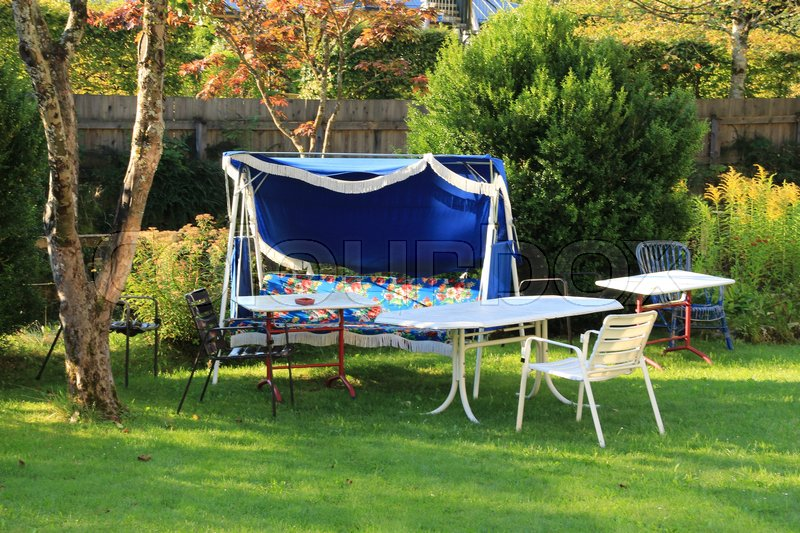 Garden furniture, a striking rocking chair with floral motif for more than one person, plastic chairs and tables in the back yard in the residential area in the village in the beautiful summer, stock photo