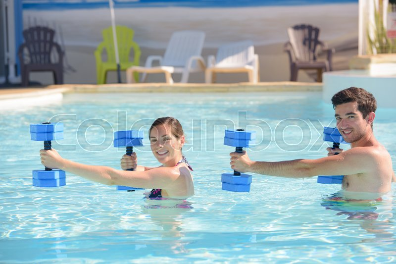 Couple doing sports under water in swimming pool, stock photo