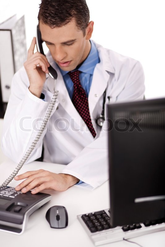 Physician Sitting At His Desk Talking Stock Photo