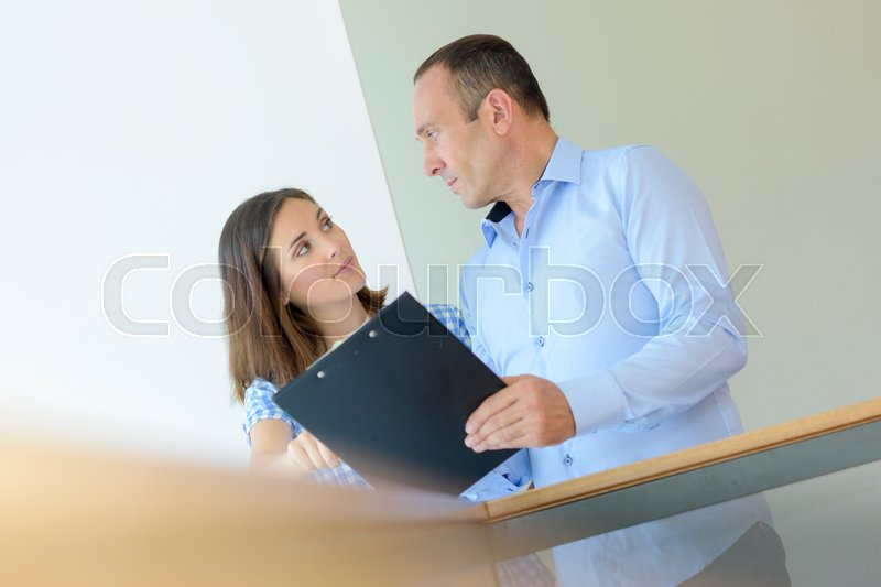 Co-workers in conversation, stock photo
