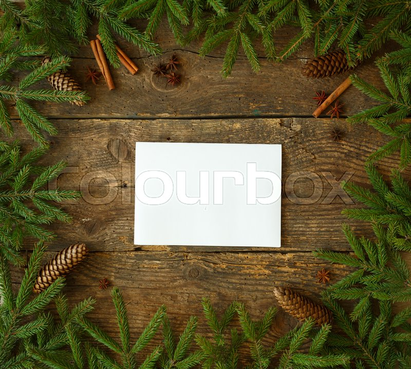 Christmas tree branch with cones, cinnamon sticks and dittany on wooden background with copyspace. Winter holiday background, stock photo