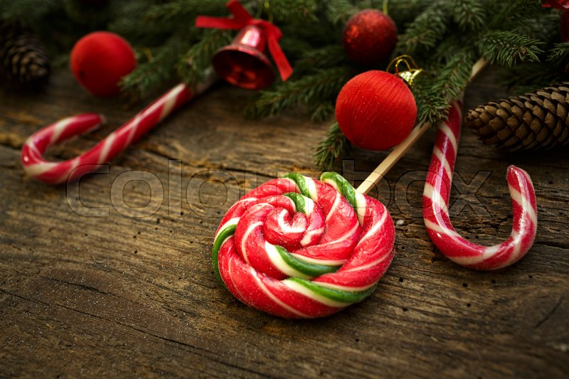 Christmas border with fir tree branches, cones, christmas decorations and candy cane on rustic wooden boards ready for your design, stock photo