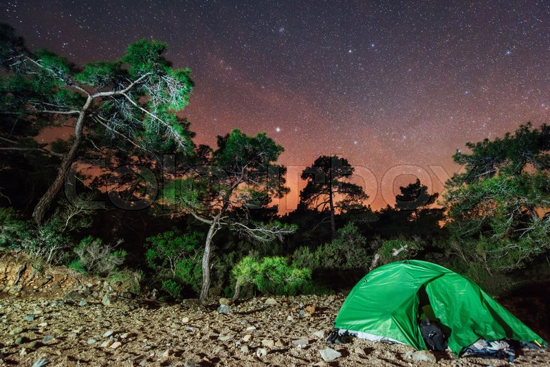 Camping under the stars. Green solo tent under dark night sky full of stars and constellations, stock photo