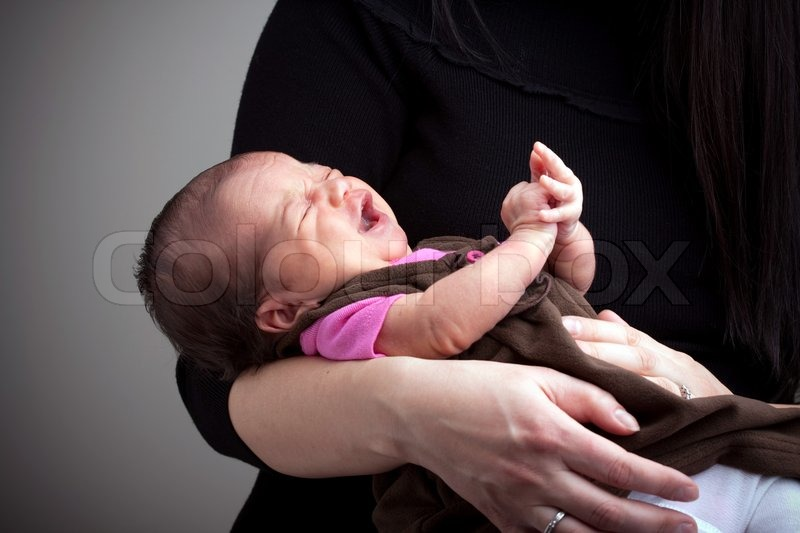 A mom holds a young newborn baby girl in her arms that is upset and crying stock photo colourbox