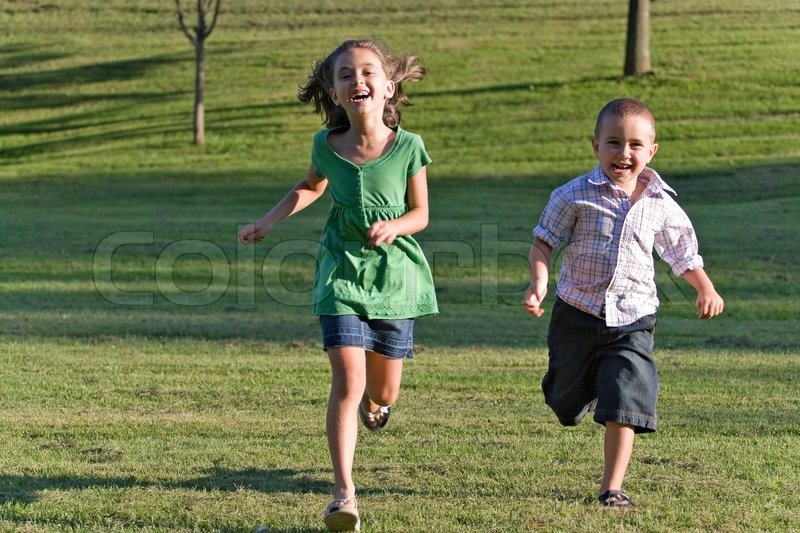 Stock image of 'Two happy little kids having fun while running through the grassy field and racing against each other'