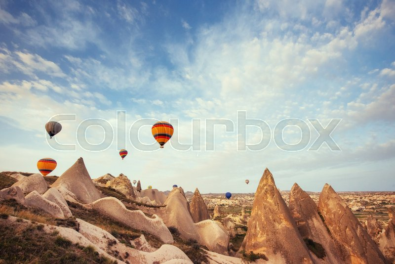 Hot air balloon flying over rock landscape at Cappadocia Turkey. Cappadocia with its valley, ravine, hills, located between the volcanic mountains in Goreme National Park, stock photo