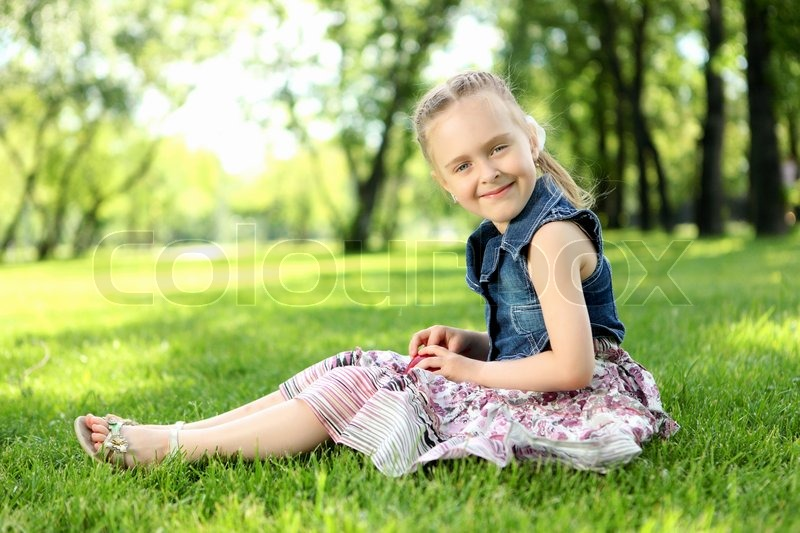 Portrait Of A Little Girl Sitting On The Grass Stock