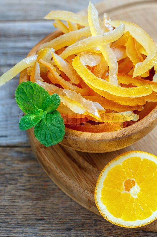 Full bowl of candied orange peel and mint on an old wooden table, stock photo