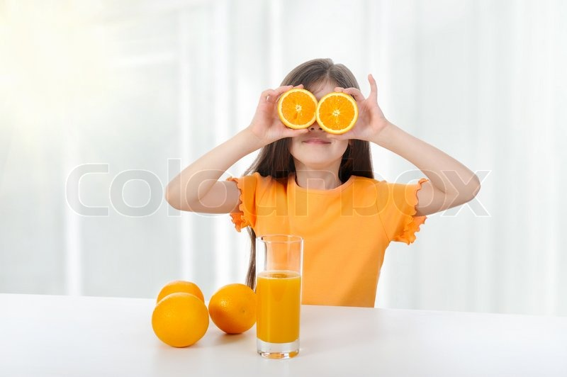 Girl at the table with oranges and juice, stock photo