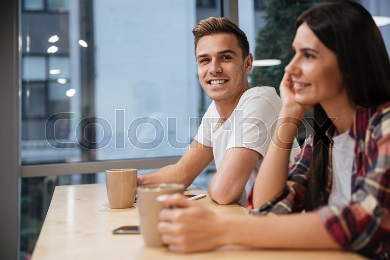 Side view of Coworkers sit by the table with coffee in office. Man looking at camera, stock photo