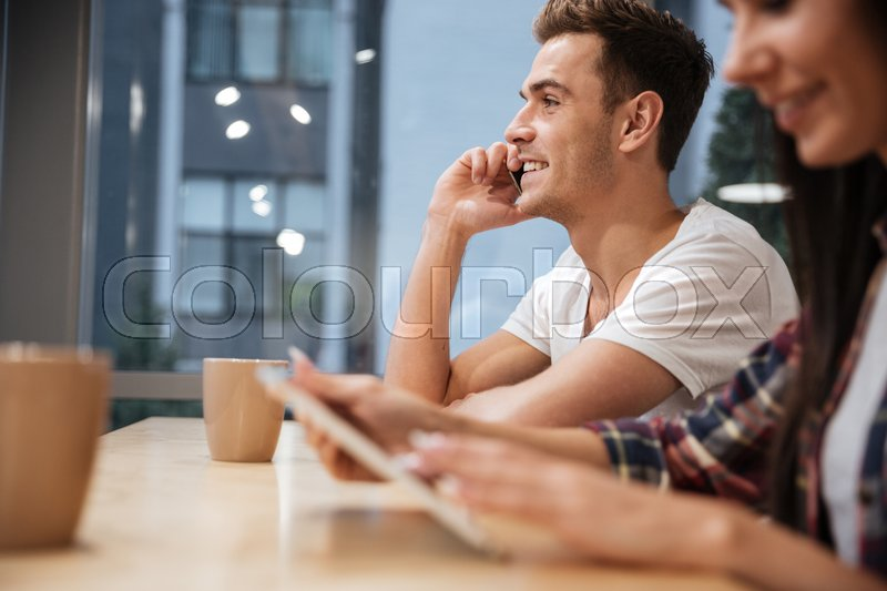 Side view of Coworkers sit by the table with coffee. Man talking at phone, girl looking on tablet computer. Focus on man. Cropped image, stock photo