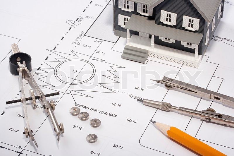 house model and drafting tools on a construction plan stock
