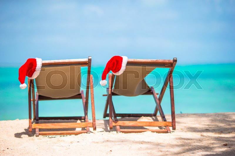 Christmas on the beach -chair lounges with Santa hats at sea. Christmas vacation concept, stock photo