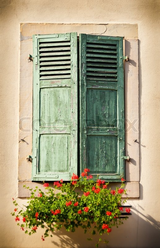 Isolated View Of A Window With Green Shutters With Flower