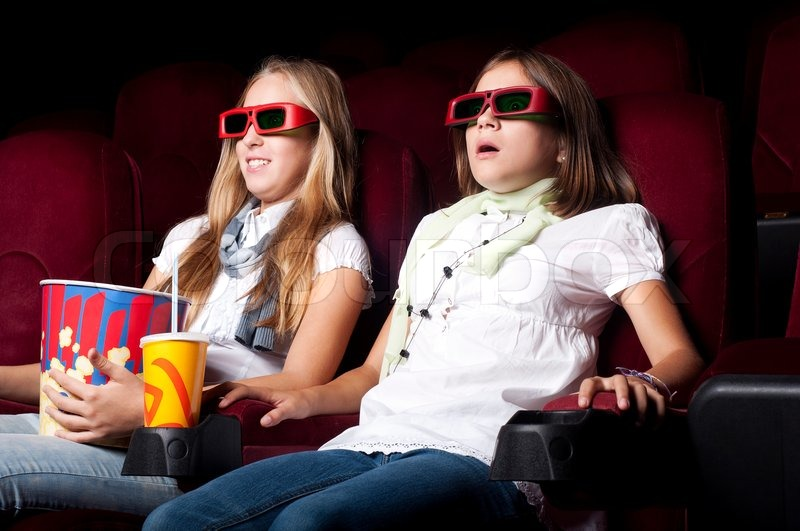 two beautiful girls watching a movie at the cinema stock