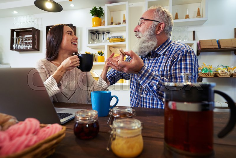 Side low angle of two people sitting at the table. Working at the laptop. Drinking tea and having fun. Spending time talking about plans or something interesting, stock photo