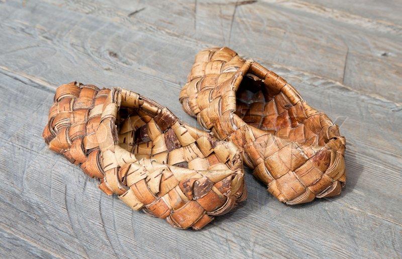 Stock foto af gamle russiske sandaler lavet af bark på trægulv
