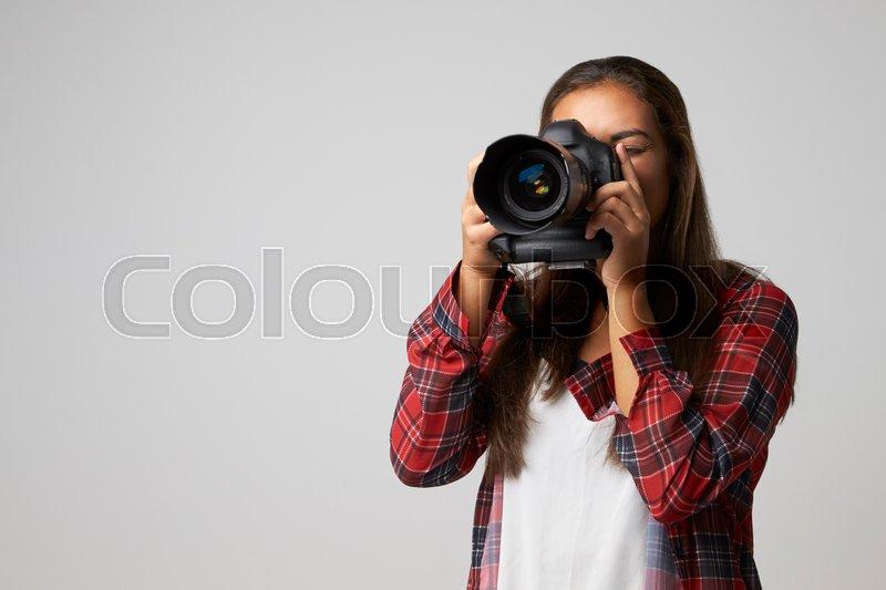 Studio Portrait Of Female Photographer With Camera, stock photo
