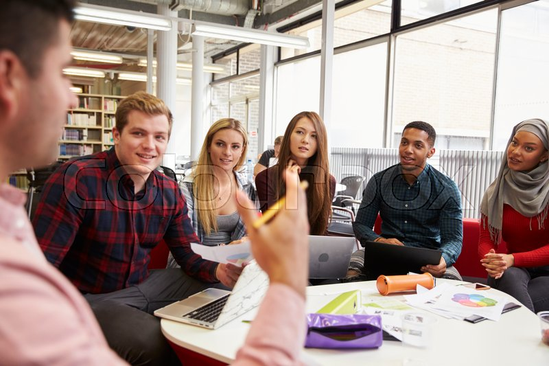 Group Of Students In Library Collaborating On Project, stock photo
