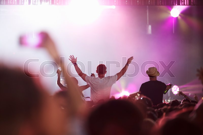 Fans Sitting On Friend\'s Shoulders At Music Festival, stock photo