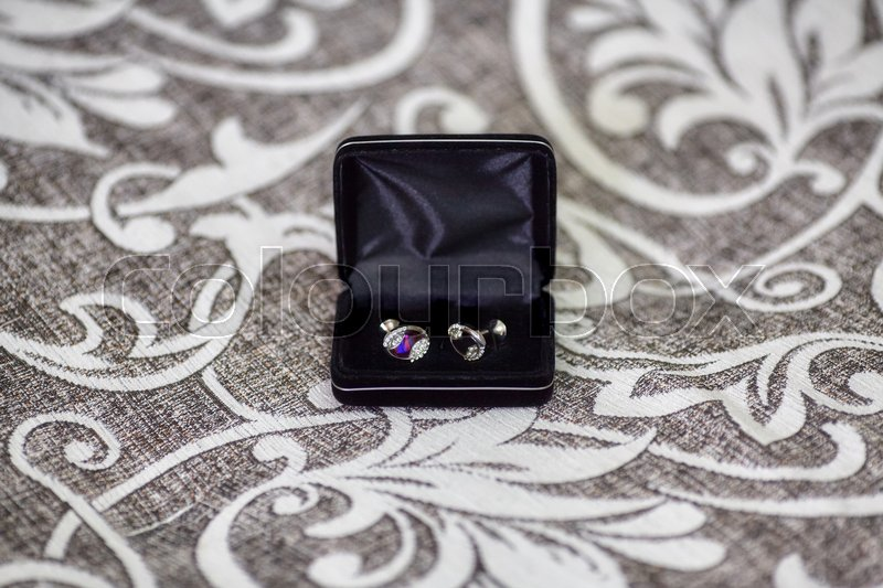 Cufflinks of groom in the black box, on sofa, stock photo