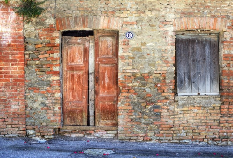 Stock image of 'Vintage wooden door and closed window in ancient brick house at Castiglione Falletto - small town in Piedmont, northern Italy'