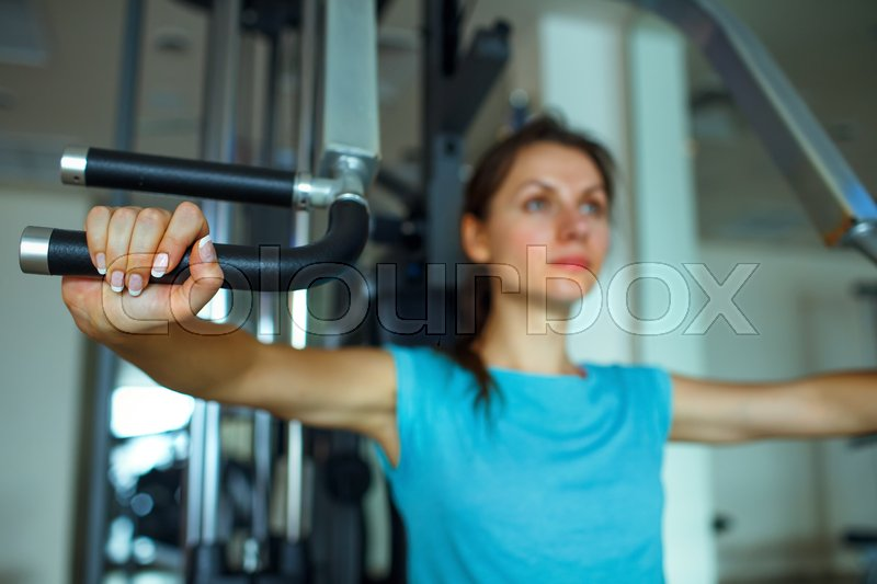 Athletic woman works out on training apparatus in fitness center, stock photo
