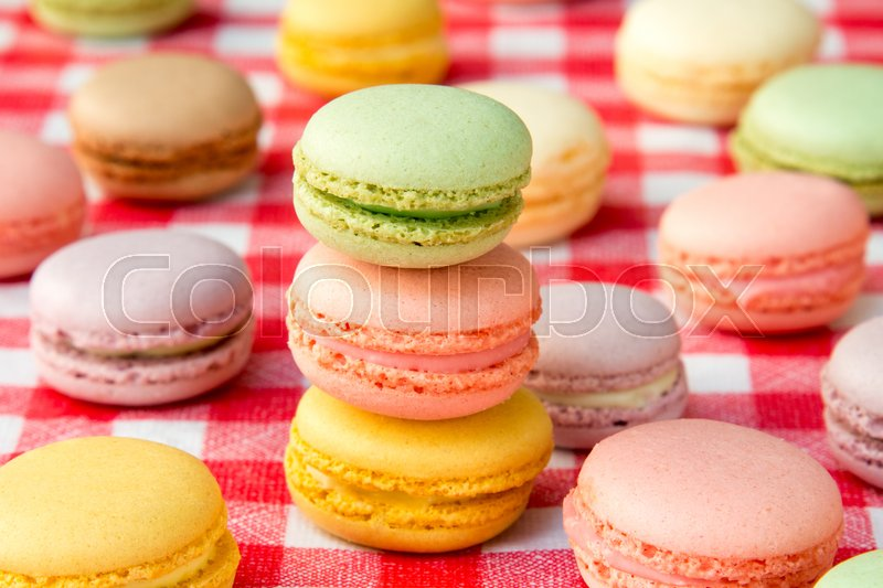 Traditional colorful french macaroons on checkered tablecloth, stock photo